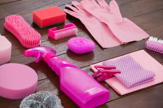 Pink color cleaning equipment arranged on wooden floor