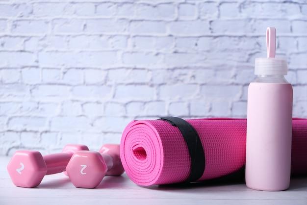 ピンク色のダンベル、運動マット、白い背景の上の水のボトル。