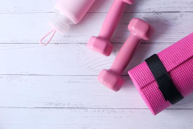 ピンク色のダンベル、エクササイズマット、ホワイトスペースのウォーターボトル。