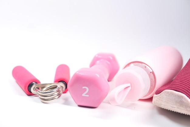 Гантели, обувь и бутылка с водой розового цвета на белом фоне.