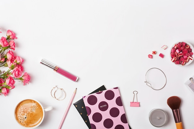 Pink colored objects, roses and coffee on the white background.