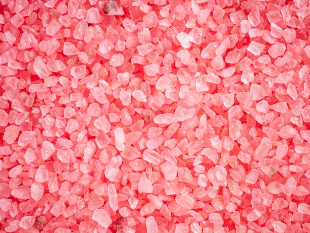 Pink colored salt crystals as a background. aromatic roseate bath salt with litchi and patchouli scent. large sprinkled crystals of crimson sea salt. beauty and body care concept. close up.