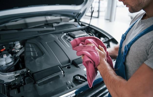 Pink colored towel. man in blue uniform works with broken car. making repairings.