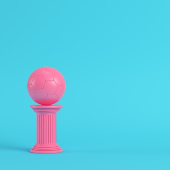 Pink column with soccer ball on bright blue background