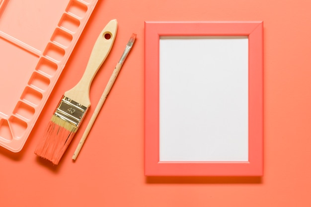 Pink composition with blank frame and drawing tools on colored surface