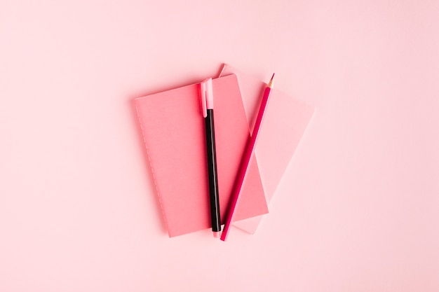 Pink composition with notebook and stationery on desk