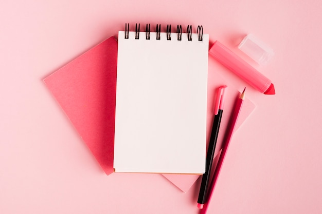 Pink composition with notepad and office supplies on colored surface