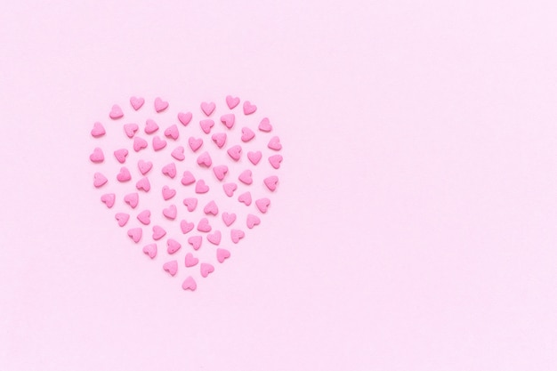 Pink confectionery sprinkles in heart shape on pastel pink background
