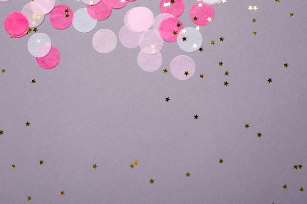 Pink confetti with gold stars on gray   with copyspace