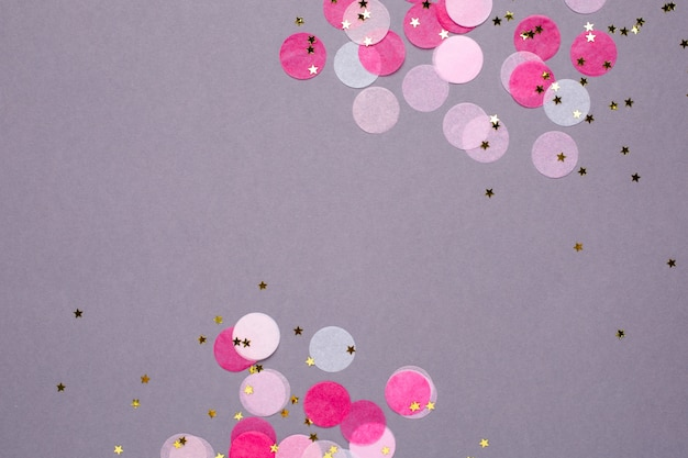 Pink confetti with gold stars on gray