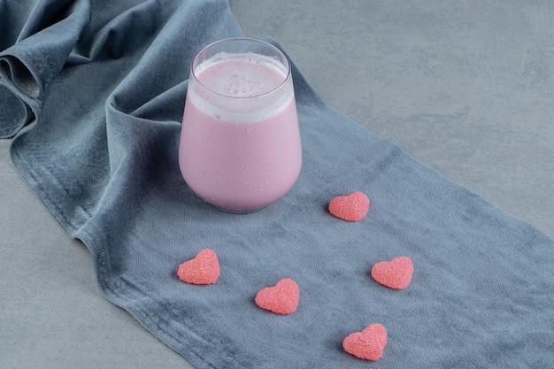 ピンクのクッキーとミルクは、大理石の背景のタオルの上で揺れます。高品質の写真