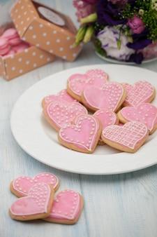 バレンタインデーにプレートとギフトボックスと花にハートの形をしたピンクのクッキー