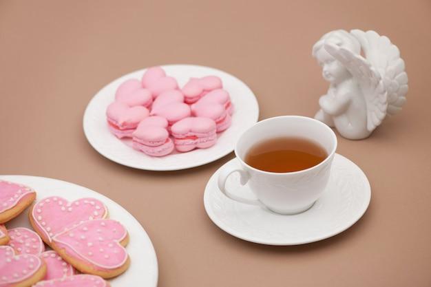 バレンタインデーにお茶と天使と一緒に皿にハートの形をしたピンクのクッキー