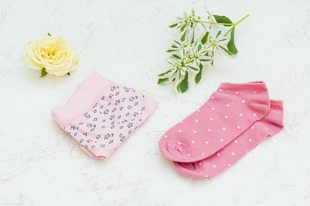 흰색 구조화된 배경에 꽃과 분홍색 여성 양말이 있는 분홍색 면 팬티. 평면도.