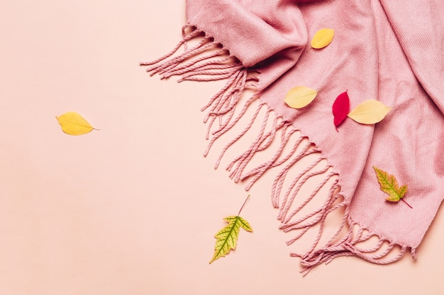 Pink cozy scarf with tassels and scattered leaves on pastel.