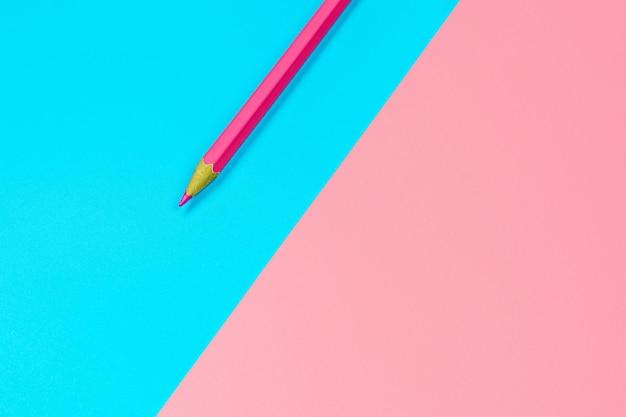青とピンクの背景にピンクのクレヨン鉛筆。