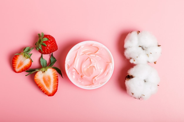 ピンクのクリームやフェイスマスク、新鮮な熟したイチゴ、ピンクの背景の綿。自然派化粧品のコンセプト。美容コンセプト。フラット横たわっていた、クローズアップ。