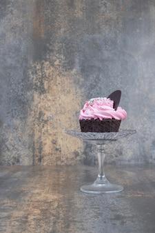 Розовый кремовый кекс на стеклянной пластине на мраморной поверхности.