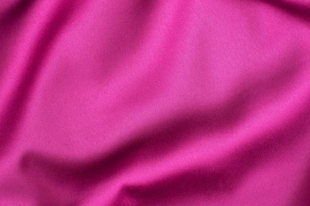 Розовая малиновая шелковая текстура, фон из материала одежды.