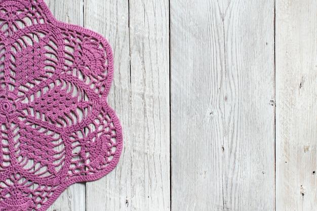 古い木製のテーブルの上のピンクのかぎ針編みのドイリー