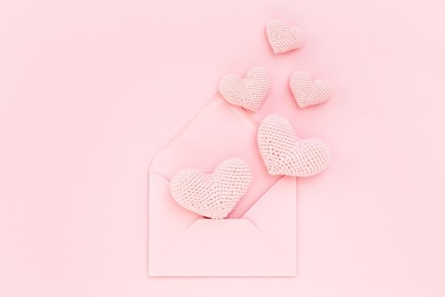 Розовые вязаные крючком сердечки в конверте на розовом фоне. день святого валентина. признание в любви. плоская планировка.