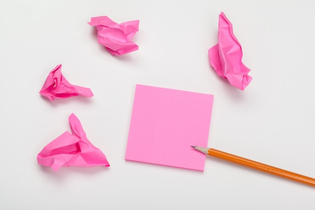 Pink crumpled papers, paper notes and pencil