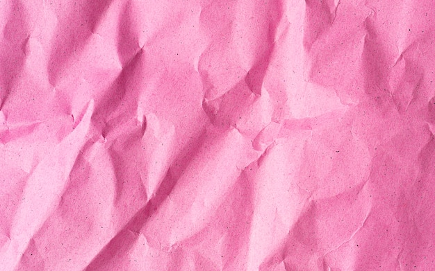 Pink crumpled recycle paper background close up with copy space