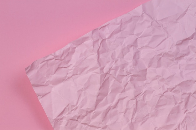 Pink crumpled wrinkled paper over blank pink paper texture background