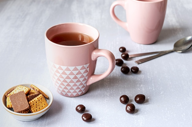 Pink cup of black tea on grey background, with cookies, chocolates and spoons.