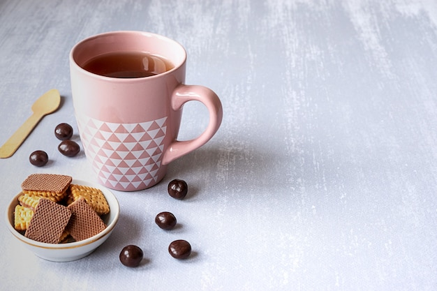 Pink cup of black tea on grey background, with cookies, chocolates and a wooden spoon. copy space.