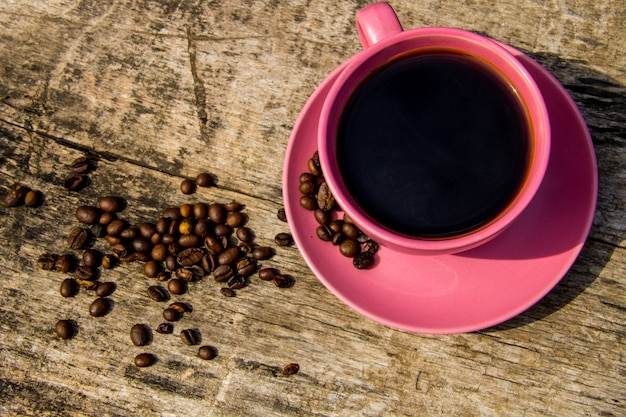 Pink cup of coffee and coffee beans on rustic wooden table. top view