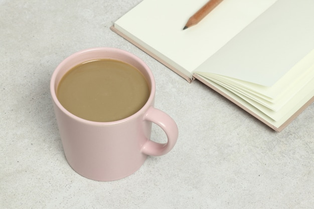 Pink cup of coffee, opened book and pencil on grey granite texture