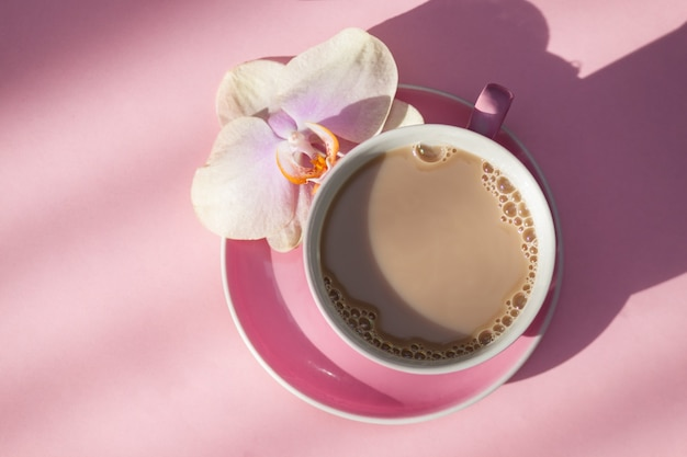 Pink cup of coffee and orchid flower on pink background. top view.