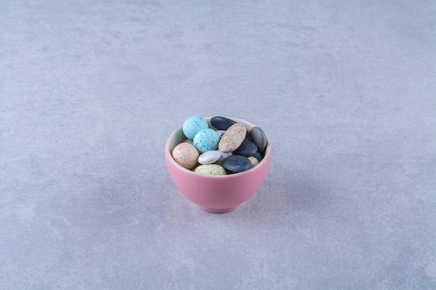 Una tazza rosa piena di caramelle colorate ai fagioli