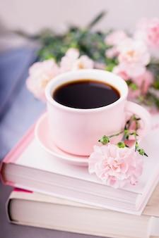 ブラックコーヒー、本、パステルピンクのカーネーションの花のピンクのカップ