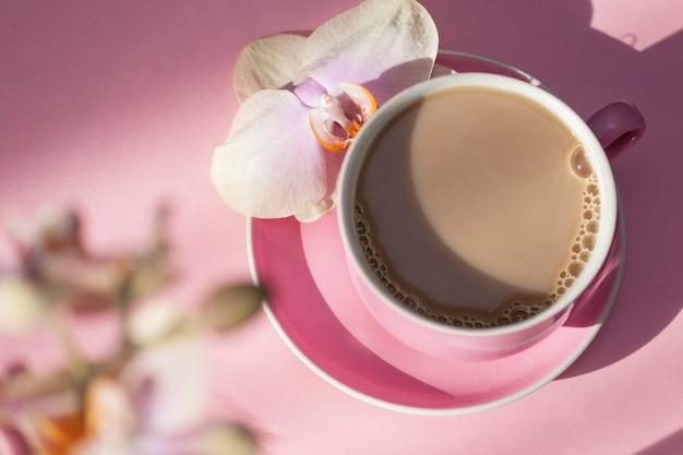 분홍색 배경에 커피와 난초 꽃의 핑크 컵. 평면도.