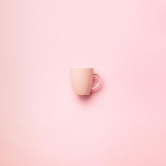 パンチのある背景の上のピンクのカップ。誕生日パーティーのお祝い、ベビーシャワーのコンセプト。パステルカラーの模様。ミニマリストスタイルのデザイン