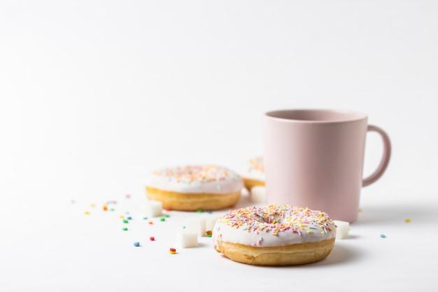 커피 또는 홍차와 신선한 맛있는 도넛, 흰색 바탕에 달콤한 다 색된 장식 사탕 핑크 컵. 베이커리 개념, 신선한 파이, 맛있는 아침 식사, 패스트 푸드.