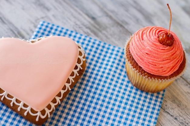 파란색 냅킨 회색 나무 테이블에 과자가 있는 분홍색 컵케이크와 하트 쿠키 디저트는 ...