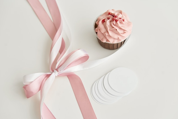 Pink cupcake on a white table with a pink bow