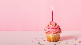 Pink cupcake with lit candle