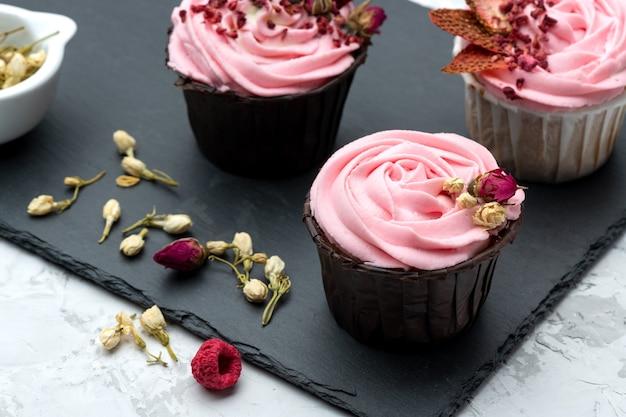 Розовые капкейки, декорированные подсолнечными ягодами и пуговицами из сухих цветов на каменной доске с текстильной салфеткой