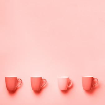 Pink cups over coral color background. top view