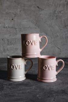 愛のピンクのカップ、灰色の背景。ロマンチックな出会い、愛、ロマンチックな朝食の概念