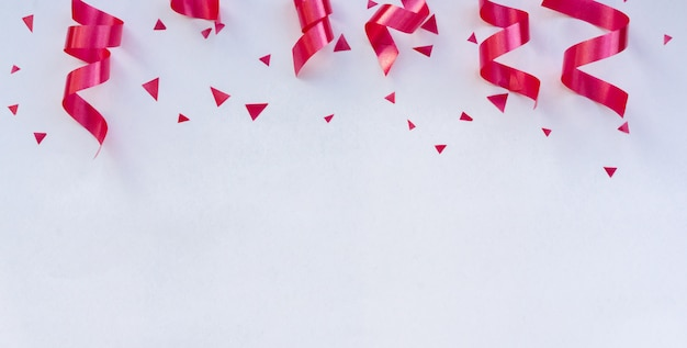 Pink curly ribbons and confetti