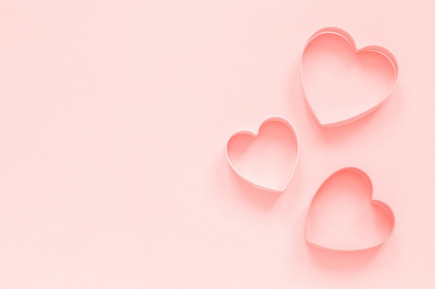 Pink cutters cookies in heart shape on pastel pink background, colar toned. love romantic pattern