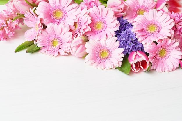 Розовые цветы герберы ромашки на белом столе. скопируйте пространство. праздничный стол.