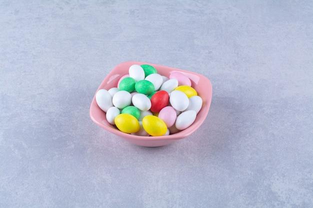 Un piatto fondo rosa pieno di caramelle colorate di fagioli sul tavolo grigio.