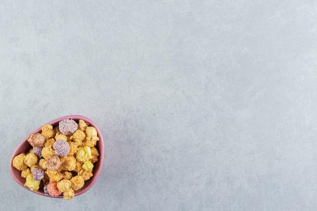 Un piatto fondo rosa di popcorn multicolori dolci.
