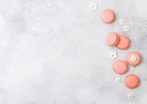 ピンクのデザートケーキマカロンまたは石造りのキッチンに白い甘い花を持つマカロン。
